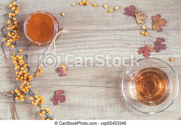 Autumn healthy hot drink concept. Branch of common sea buckthorn with berry, cup of tea, jar of jam on light wooden background - csp55453346