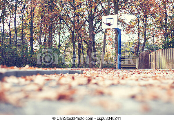 Autumn in a park with basketball court - csp63348241