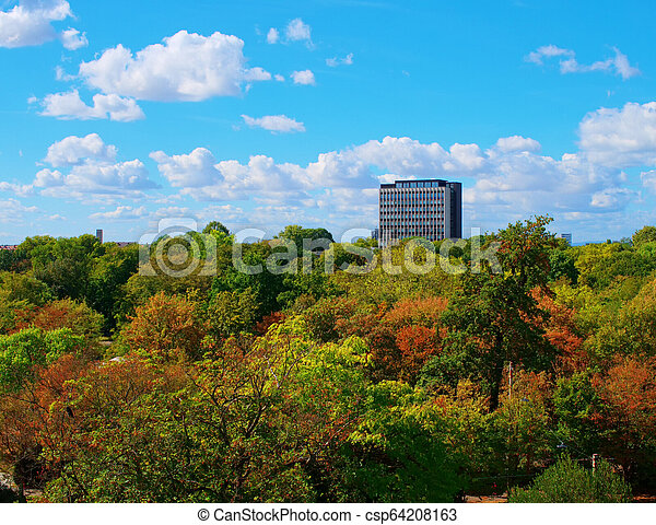 autumn in the city skyscraper surrounded by forest - csp64208163