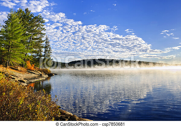 Autumn lake shore with fog - csp7850681