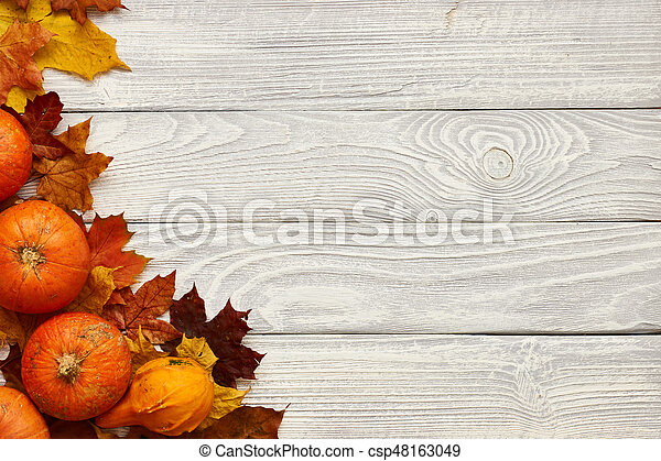 Autumn leaves and pumpkins over old wooden background - csp48163049