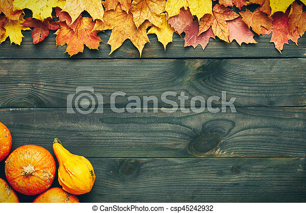 Autumn leaves and pumpkins over old wooden background - csp45242932