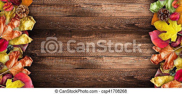 Autumn Leaves over a Natural Dark Wooden background. Old dirty wood tables or parquet with knots and holes and aged partculars. - csp41708268