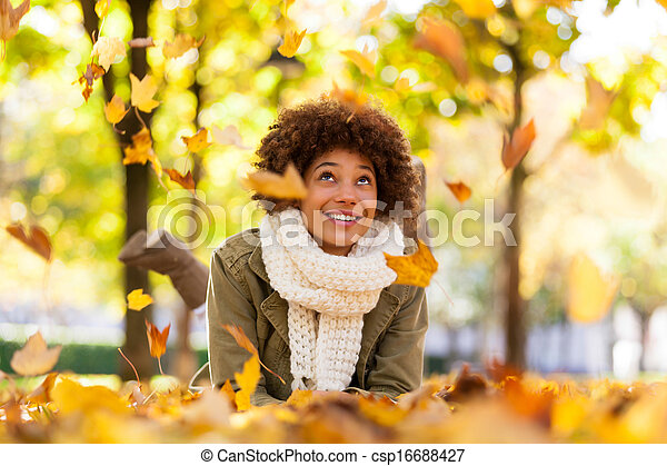 Autumn outdoor portrait of beautiful African American young woman lying down - Black people - csp16688427