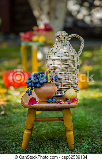 Autumn scene with plants, pumpkins, apples in a wicker basket, ceramic pots, wooden chair, vintage style, composition in the garden. - csp62589134