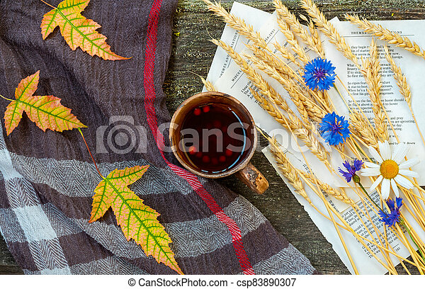 Autumn still life with a cup of tea, ears of wheat, cornflowers, a warming scarf and colorful leaves - csp83890307