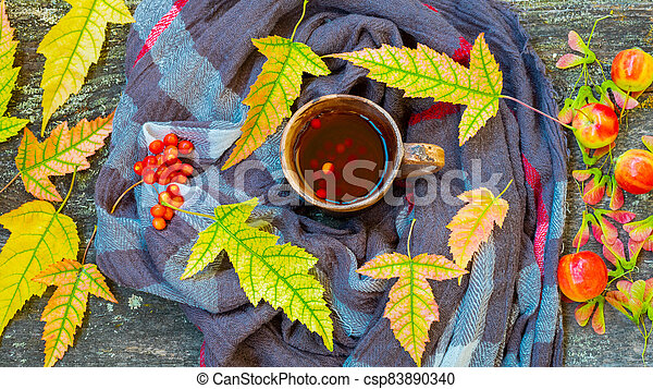 Autumn still life with cup of tea, warming scarf and colorful leaves over rustic wooden background - csp83890340