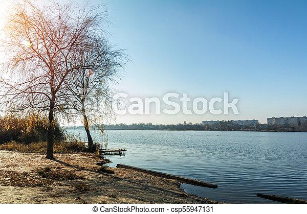 Autumn sunny landscape. Beach with a pier near the river - csp55947131