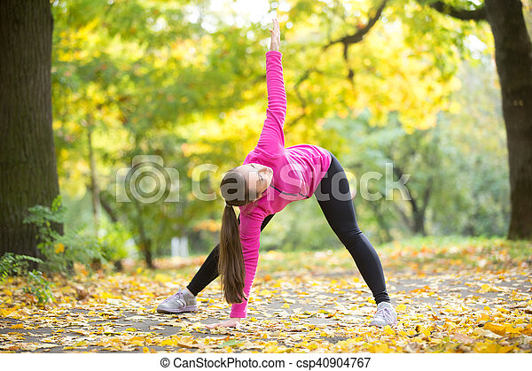 autumn yoga triangle pose portrait of sporty beautiful