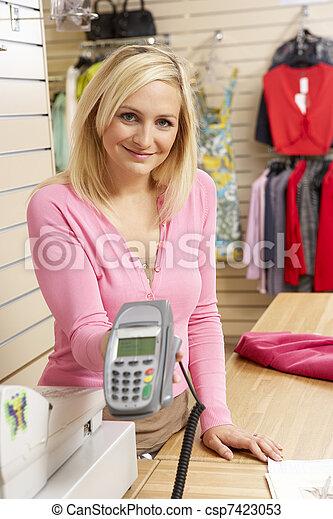 Asistente de ventas femenina en la tienda de ropa - csp7423053