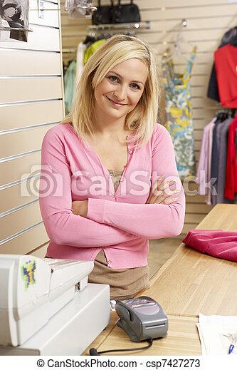 Asistente de ventas femenina en la tienda de ropa - csp7427273