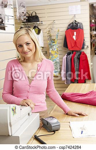 Asistente de ventas femenina en la tienda de ropa - csp7424284