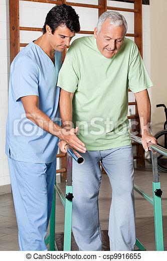 Terapeuta asistiendo al hombre mayor a caminar con el apoyo de los bares - csp9916655