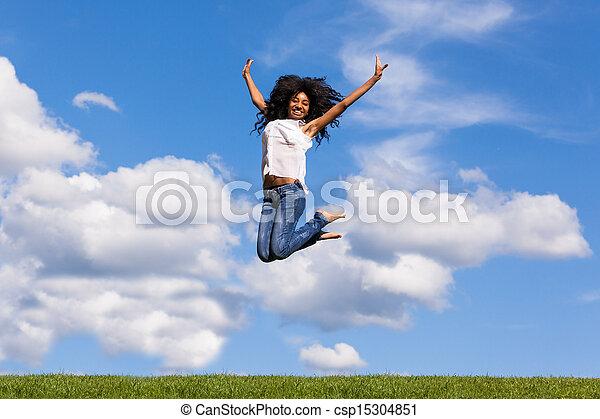 Un retrato al aire libre de una joven negra sonriente saltando sobre un cielo azul, gente africana - csp15304851