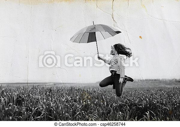 Chica adolescente saltando en el campo verde en un fondo de cielo azul - csp46258744