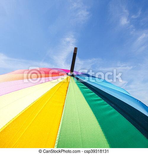 Una sombrilla arco iris de colores en el fondo del cielo azul - csp39318131