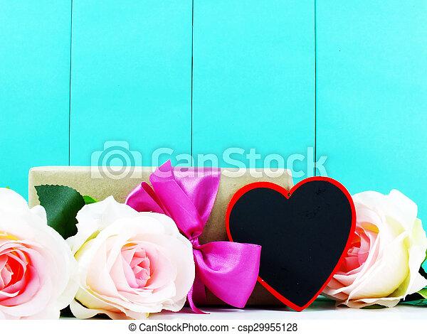 El corazón y las rosas flor con caja de regalo en el fondo azul - csp29955128