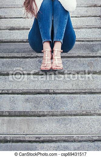 Una mujer joven con zapatos de tacón alto y vaqueros azules