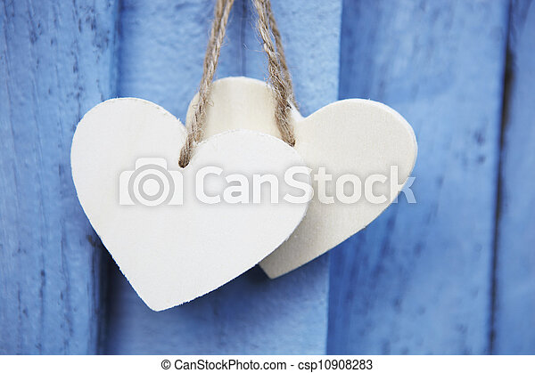 Dos corazones de madera colgando en la superficie azul de madera - csp10908283