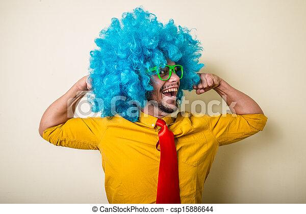 Un joven loco y divertido con peluca azul - csp15886644