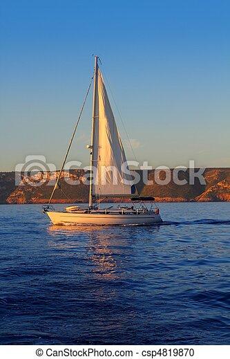 Barco navegando dorado amanecer en el océano azul - csp4819870