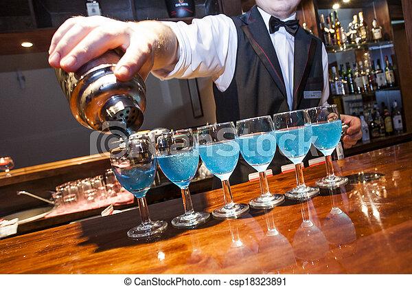 Camarero, camarero, sirviendo bebidas de color azul desde el agitador hasta la fila de vasos en el mostrador de la barra, fragmentos visibles de la mano, agitador y barman. No hay necesidad de relase modelo. - csp18323891