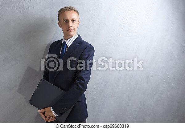 Portarit del joven caucásico con traje azul posando con portátil contra la pared grunge. - csp69660319