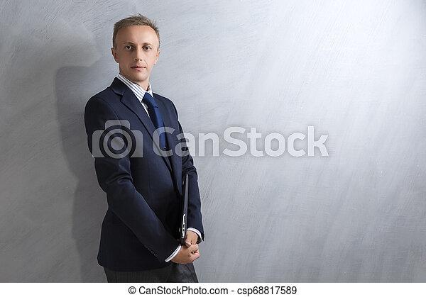 Portarit del joven caucásico con traje azul posando con portátil contra la pared grunge. - csp68817589