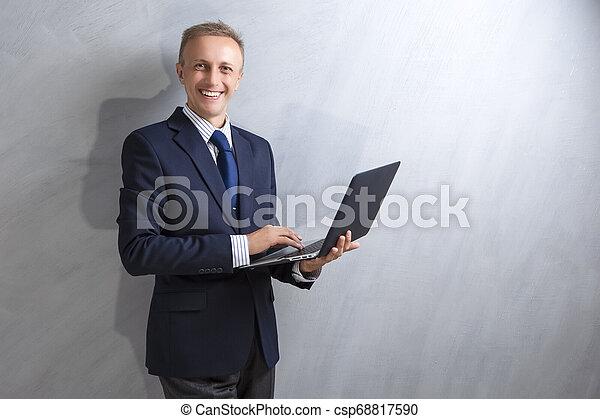 Portarit de sonriente hombre caucásico con traje azul trabajando con portátil contra pared grunge. - csp68817590