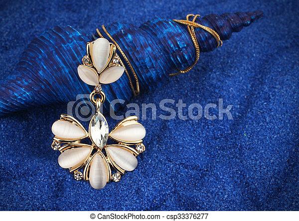Un colgante de joyas con nacre y diamantes en fondo azul marino - csp33376277