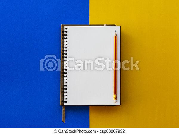 Una libreta blanca con lápiz aislado en dos tonos amarillo y azul. - csp68207932