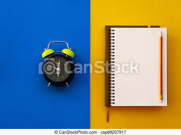 Una libreta blanca con lápiz y despertador aislados en dos tonos amarillo y azul. - csp68207917