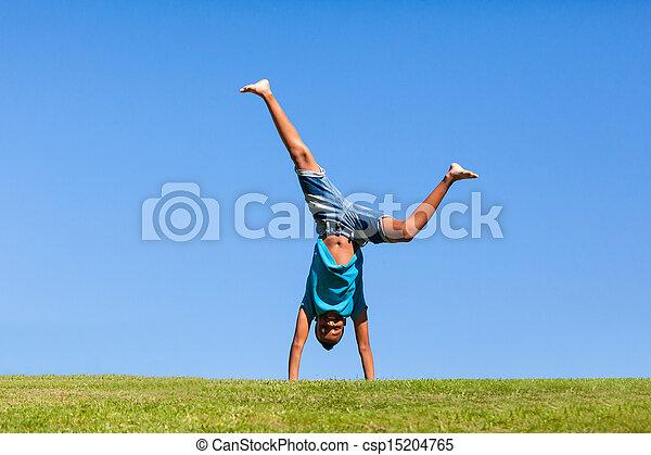 Retrato al aire libre de un hermoso adolescente negro saltando sobre un cielo azul gente africana - csp15204765