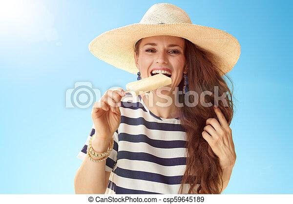 Una joven sonriente contra un cielo azul mordiendo helado - csp59645189
