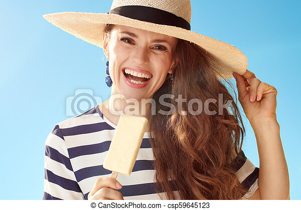 Una joven feliz contra un cielo azul comiendo helado - csp59645123