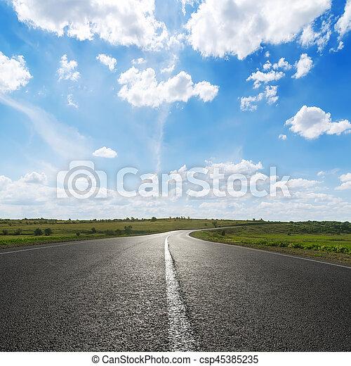 Cielo azul con nubes blancas sobre la carretera de asfalto - csp45385235