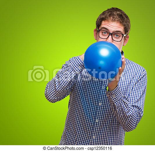 Retrato de hombre soplando globo azul - csp12350116