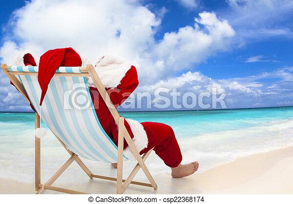 Santa Claus sentado en sillas de playa con cielo azul y nubes - csp22368174