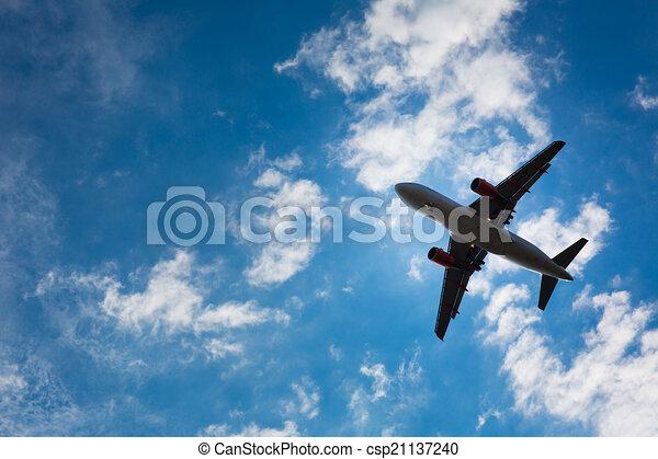 Silueta oscura de un avión volando sobre los cielos azules - csp21137240