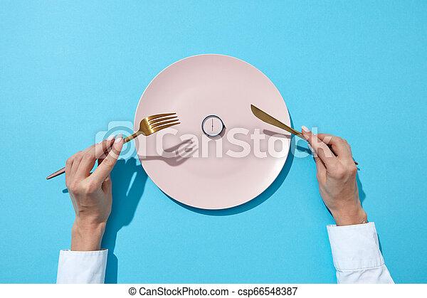 Placa blanca con lo quecho redondo muestra a las seis servido cuchillo y tenedor en las manos de una chica en un fondo azul. Hora de comer y el concepto de dieta. La mejor vista. - csp66548387
