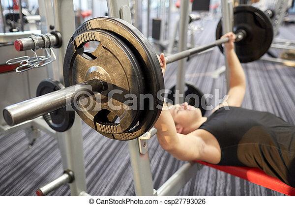 Cerca del hombre flexionando bíceps con pesas en el gimnasio - csp27793026
