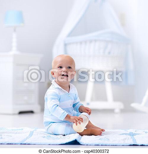 Baby boy drinking milk in sunny nursery - csp40300372
