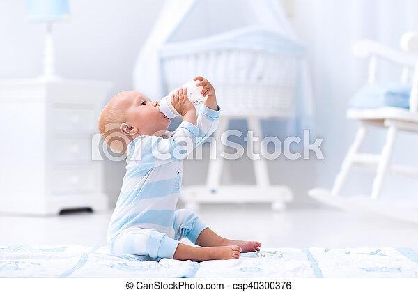 Baby boy drinking milk in sunny nursery - csp40300376