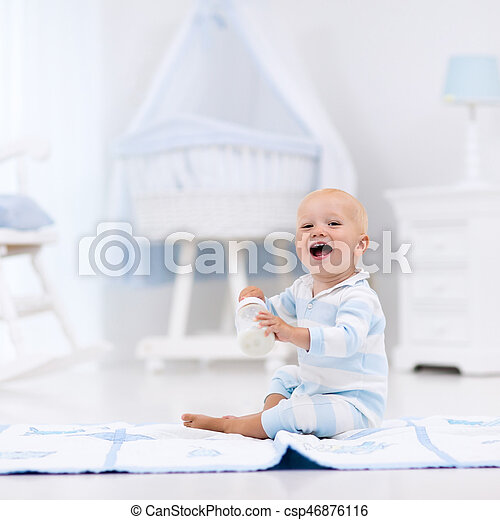 Baby boy drinking milk in sunny nursery - csp46876116