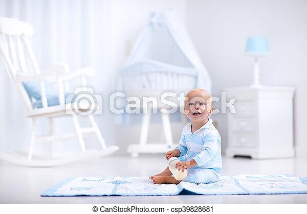 Baby boy drinking milk in sunny nursery - csp39828681