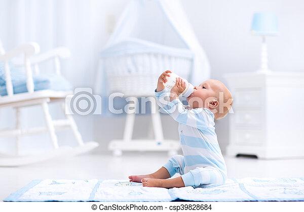 Baby boy drinking milk in sunny nursery - csp39828684
