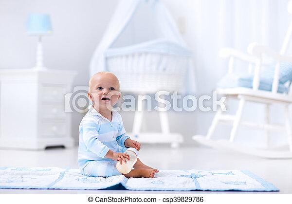 Baby boy drinking milk in sunny nursery - csp39829786