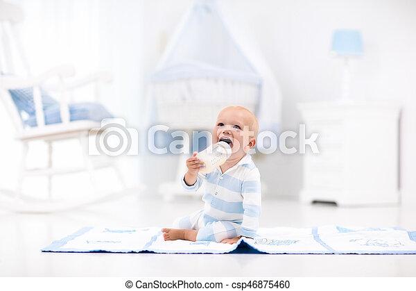 Baby boy drinking milk in sunny nursery - csp46875460