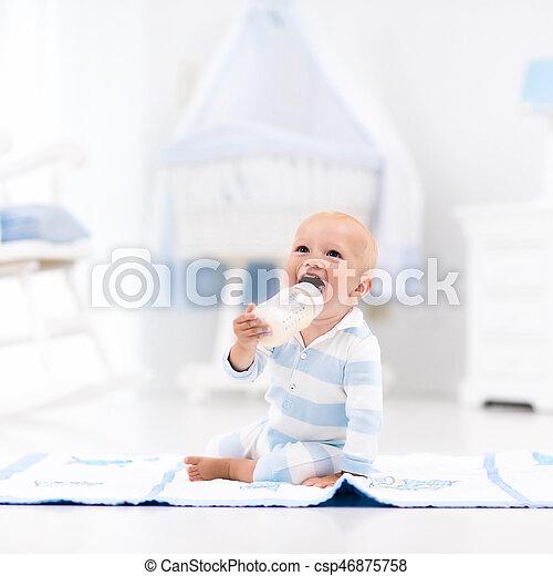 Baby boy drinking milk in sunny nursery - csp46875758