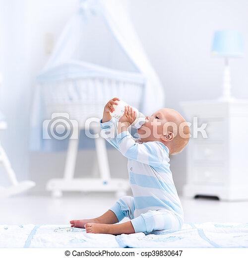 Baby boy drinking milk in sunny nursery - csp39830647